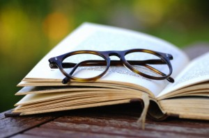 Old reading glasses with a book in the garden